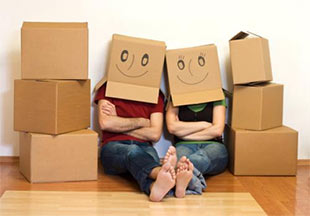 couple with moving boxes with smiley faces on their heads